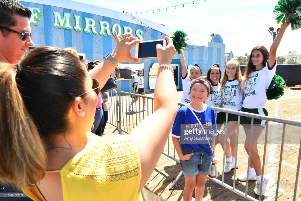 "SANTA MONICA, CALIFORNIA - JUNE 29: Fans are greeted by Hawkins High School cheerleaders at the Netflix's ""Stranger Things"" Season 3 Fun Fair at Santa Monica Pier on June 29, 2019 in Santa Monica, California. (Photo by Amy Sussman/Getty Images)"